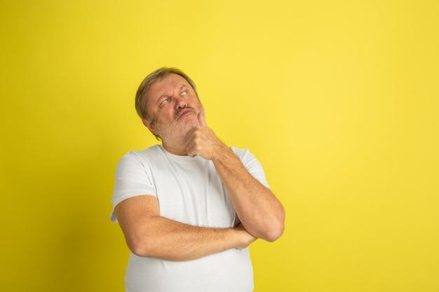 Задумчивый, мечтательный. портрет кавказского человека, изолированные на желтом фоне студии. красивая мужская модель в белой рубашке позирует. понятие человеческих эмоций, выражения лица, продаж, рекламы. copyspace.