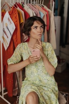 Thoughtful dreamily short-haired brunette woman in floral dress looks up