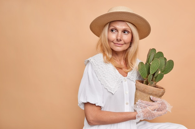 Thoughtful dreamy middle aged aristocratic woman looks away bought potted cactus for her home garden likes houseplants wears fedora white fashionable dress and lacy gloves isolated over beige wall