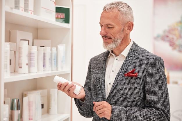Задумчивый пожилой мужчина смотрит на маленькую белую бутылку в магазине