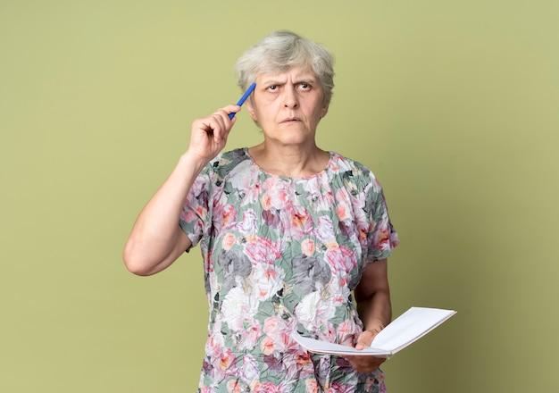 思いやりのある年配の女性は、ノートを保持し、オリーブグリーンの壁に隔離された寺院にペンを置きます