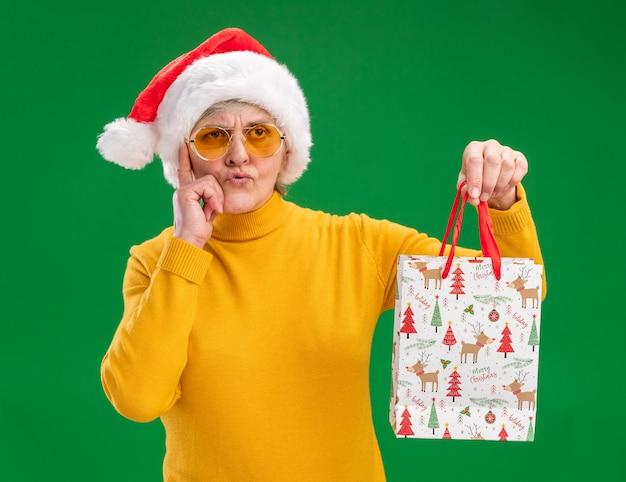 Задумчивая пожилая женщина в солнцезащитных очках в шляпе санта-клауса кладет палец на храм и держит бумажный подарочный пакет, глядя в сторону, изолированную на зеленом фоне с копией пространства