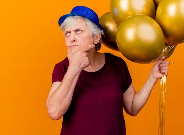 パーティーハットをかぶった思いやりのある年配の女性は、あごに手を置き、オレンジを見上げてヘリウム気球を保持します