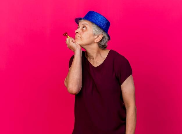 パーティーハットをかぶった思いやりのある年配の女性は、ピンクを見上げる笛を持っているあごに手を置きます