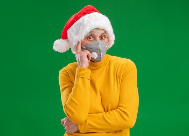 Premurosa donna anziana con cappello santa indossando maschera medica mette il dito sul tempio e guarda la telecamera isolata su sfondo verde con copia spazio