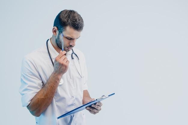 Заботливый европейский мужской доктор читая что-то в буфере обмена. молодой бородатый человек со стетоскопом в белом халате. изолированные на сером фоне с бирюзовым светом. студийная съемка. скопируйте пространство.
