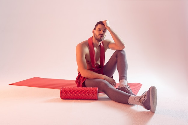 Вдумчивый европейский спортсмен сидит на фитнес-коврике с лентой сопротивления. молодой красивый бородатый мужчина с обнаженным спортивным торсом. изолированные на бежевом фоне. студийная съемка. копировать пространство
