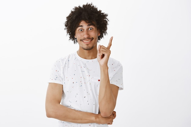Thoughtful and excited man having an idea, raising finger in eureka gesture