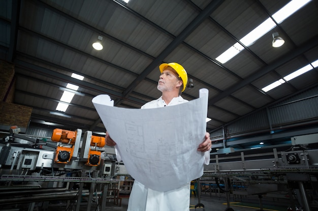 Thoughtful factory engineer holding blueprint