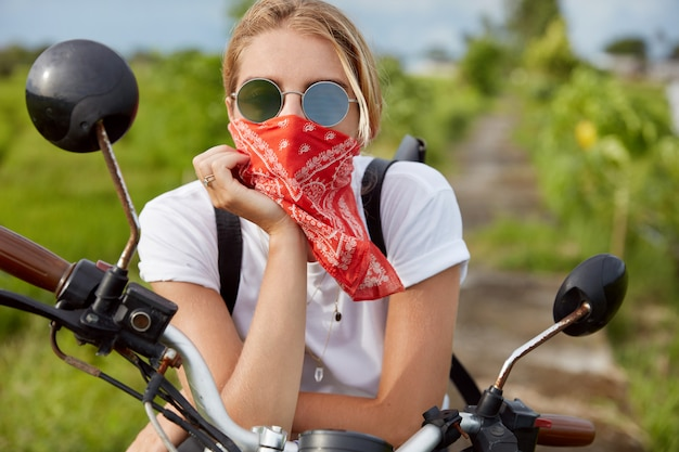 Thoughtful fashionable female biker rests on motorbike, wears sunglasses and bandana covered on mouth, has fast ride on green field, enjoys fresh air and good day. outdoor traveling concept