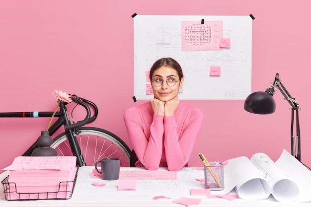 Thoughtful female architect plans new project makes sketches and blueprints enjoys creative solutions in mind has productive job sits at desktop works from home plans interior of future building