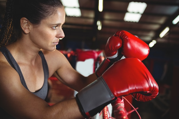 Thoughtful female boxer leaning on boxing ring