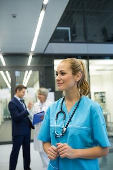 Вдумчивый женщина-врач, стоя в коридоре