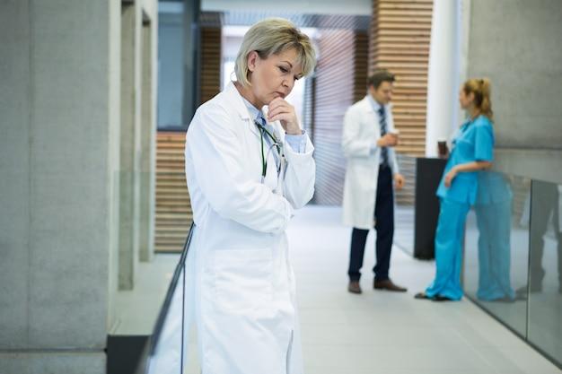 N廊下に立っている思いやりのある女性医師