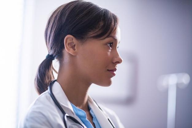 Вдумчивый женщина-врач со стетоскопом в палате