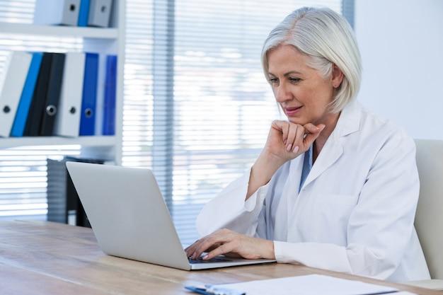 Вдумчивый женский доктор работает на своем ноутбуке