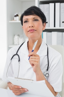 Задумчивый женщина-врач, пишущий в буфере обмена