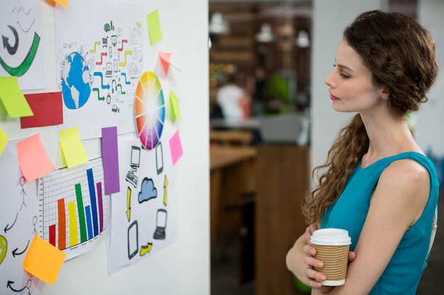 Thoughtful female executive looking at sticky notes on white wall