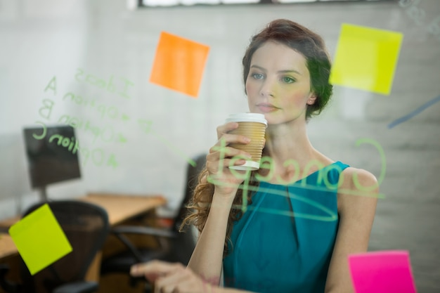 Thoughtful female executive looking at sticky notes