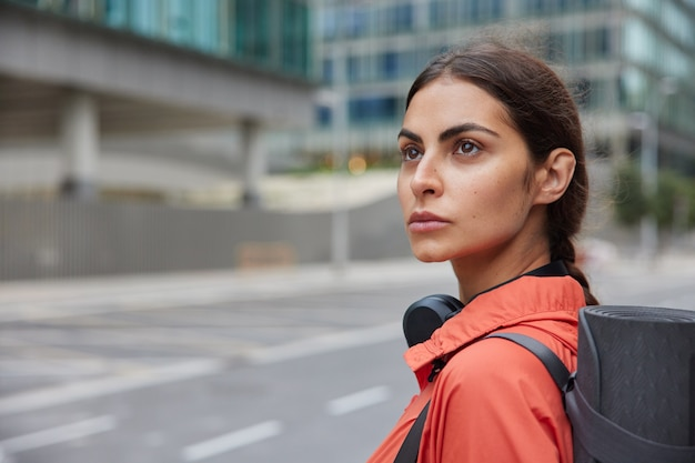 Thoughtful female fitness trainer prepares for jogging workout strolls at urban street with karemat on shoulder does regular sport in fresh air to reduce risk of heaart disease