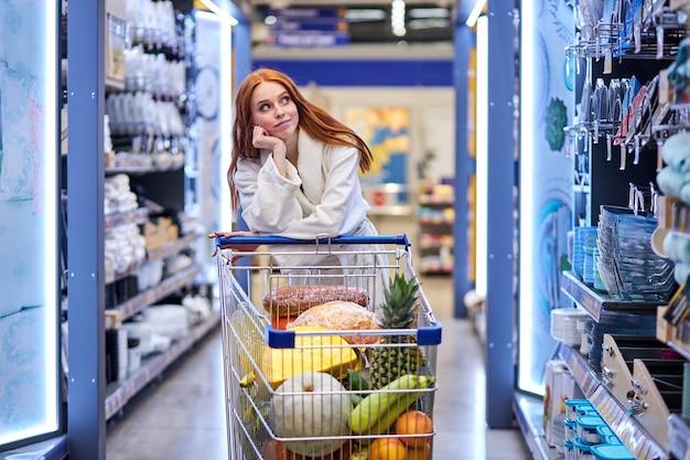 Задумчивая женщина в отделе посуды, выбирает тарелки и сковороды для дома, одна, в халате. в супермаркете