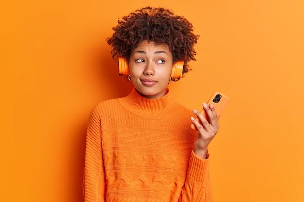 사려 깊은 여성 멜로 맨이 재생 목록의 오디오 트랙을 듣고 현대 스마트 폰을 옆으로 쳐다 보며