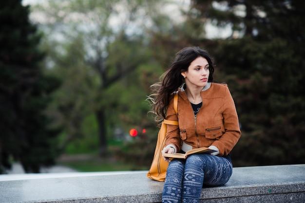 春休みの暇な時間に読んでいる本を思いやりのある女性、秋の公園に座って何か良いことを夢見る豪華な若い女性