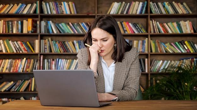 사려 깊은 여성 프로젝트 관리자는 사무실의 나무 책장에 기대어 갈색 테이블에 앉아 노트북 디스플레이와 유형을 보고 있는 펜을 들고 있습니다.
