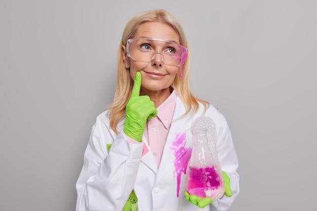 Задумчивая женщина-исследователь держит фляжку с розовыми пузырьками жидкости, держит палец на лице, носит прозрачные очки, белое пальто, изолированное на сером