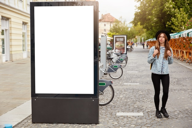 Thoughtful female tourist strolls on footway near lightbox with mock up blank space for your advertising content or commercial information. street style concept. focus on billboard at sidewalk
