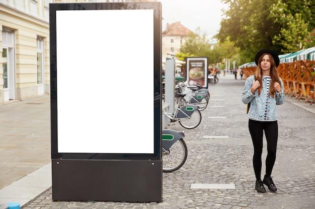 Turista femminile premurosa passeggia sul marciapiede vicino al lightbox con uno spazio vuoto per i tuoi contenuti pubblicitari o informazioni commerciali. concetto di stile di strada. concentrarsi sul tabellone per le affissioni al marciapiede
