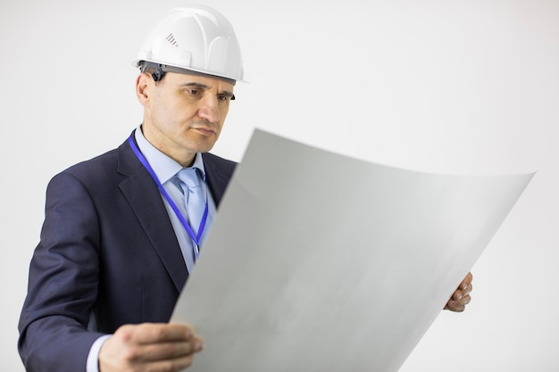 Thoughtful and focused on constructor in helmet formal clothing look at drawing