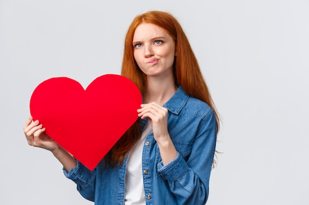 Thoughtful and focused, serious-looking redhead girl trying think, smirk indecisive and unsure, looking up pondering, holding big red valentines day heart, white