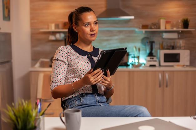 Вдумчивая внештатная женщина с помощью планшетного пк во время сверхурочной работы на домашней кухне. используя современные технологии в полночь, сверхурочно на работе, в бизнесе, занятом, в карьере, в сети, в образе жизни, в беспроводной сети.