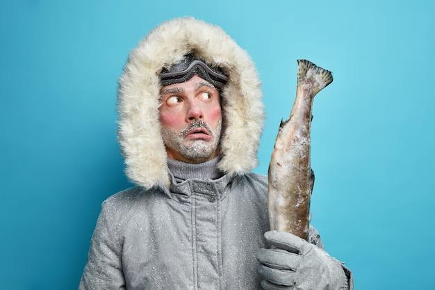 思慮深い凍った無精ひげを生やした男は、氷の湖で捕れた大きなトロフィーの魚を保持し、冬の間はジャケットを着て活発な休息をとっています。