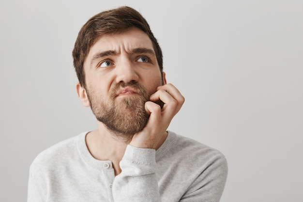 Thoughtful funny guy scartching beard and thinking