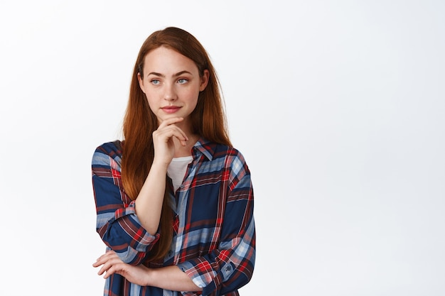 Thoughtful ginger girl with freckles, making choice on white