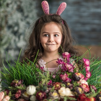 Thoughtful girl in bunny ears with flowers