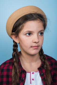Thoughtful girl in hat with pigtails