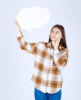 白い壁に空のテキストの雲を見ている思いやりのある女の子。