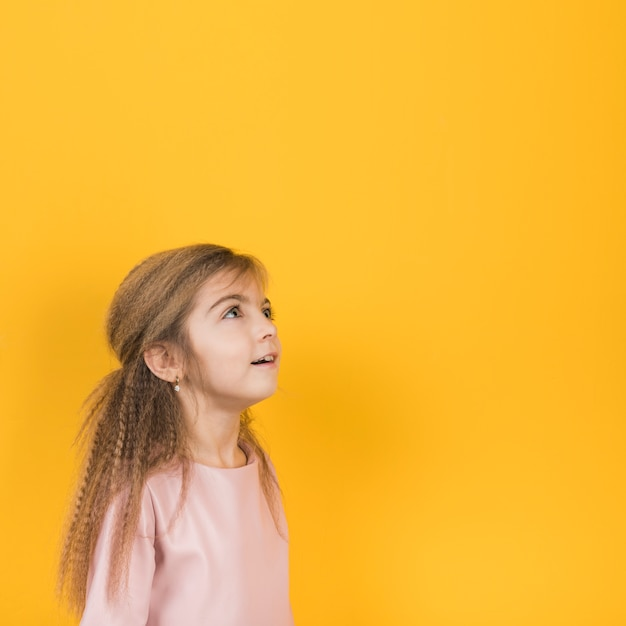 Thoughtful girl looking up on yellow background