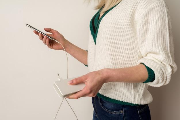 사려 깊은 소녀가 전화기에서 놀고 보조 배터리로 감염시킵니다. 여자의 손에 전원 은행. 파워 뱅크 사용 및 게임.