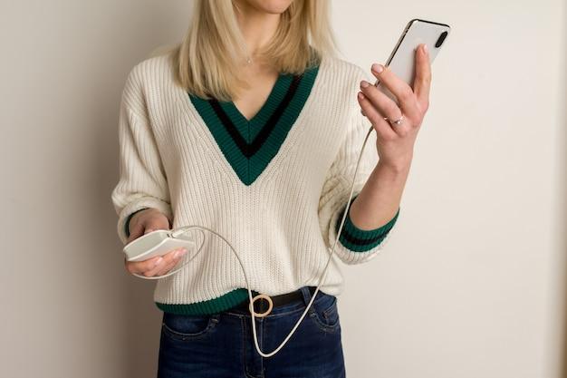 사려 깊은 소녀가 전화기에서 놀고 보조 배터리로 감염시킵니다.