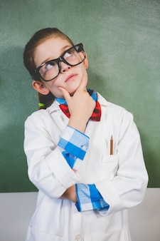 Thoughtful girl standing with hand on chin in classroom
