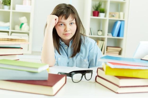 Задумчивая девушка в окружении книг