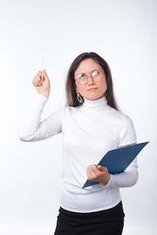 眼鏡をかけている思いやりのある女の子は、紙のクリップボードとペンを持っています。