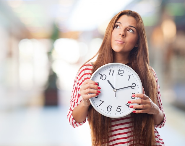 Thoughtful girl with a clock