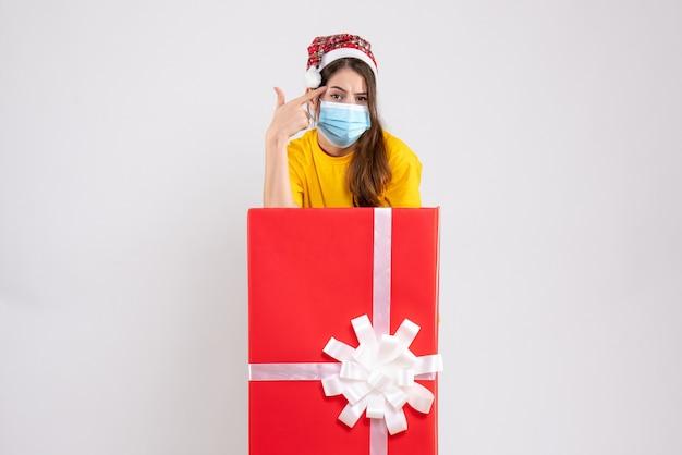 화이트에 큰 크리스마스 선물 뒤에 서 손가락 총을 만드는 산타 모자와 사려 깊은 소녀