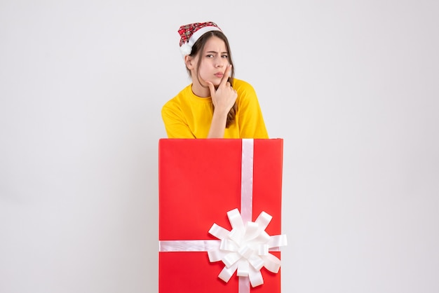 白の大きなクリスマスプレゼントの後ろに立っているサンタの帽子を持つ思いやりのある女の子