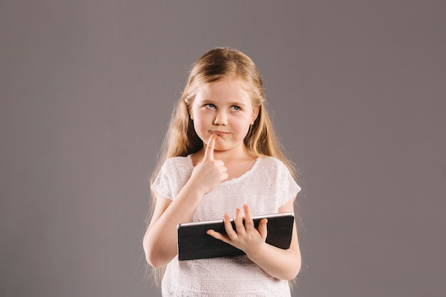 Thoughtful girl with tablet